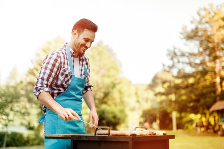 Handsome male prepares barbecue outdoors Imagens