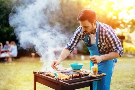 Knappe mannelijke het voorbereiden barbecue buiten voor vrienden Stockfoto