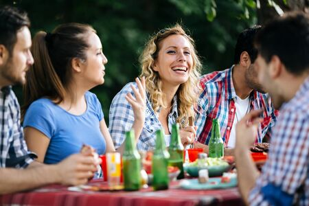 barbecuing: Friends eating outdoors and having fun after barbecuing