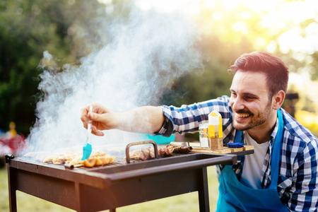 ハンサムな男性の友人の屋外バーベキューの準備
