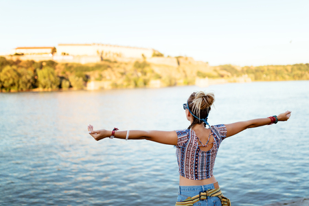 freely: Woman freely spreads arms and enjoys river flow Stock Photo
