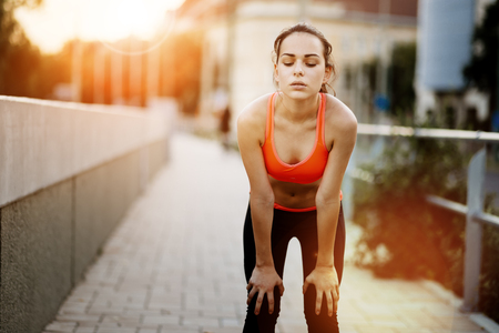 tired person: Tired female jogger resting after finishing run Stock Photo