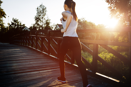 Beautiful scene of female jogger crossing bridge