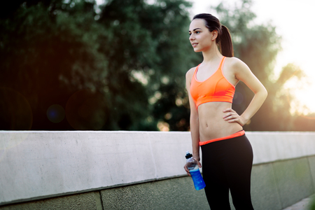 Female runner resting and drinking water Stock Photo