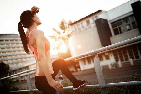 Tired female jogger resting after finishing run Stock Photo