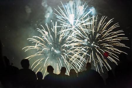glow pyrotechnics: Crowd wathcing fireworks and celebrating Stock Photo