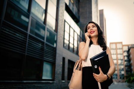 phone professional: Businesswoman carrying folders and talking on phone