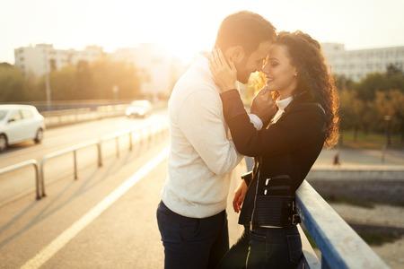 美しいカップルが日没時に屋外キス