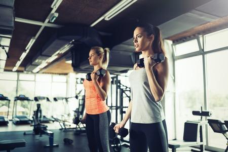 Vrouwen die samen in gymnastiek uitwerken, gewichten opheffen