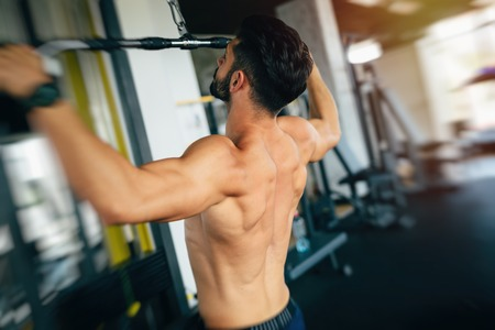 masculinity: Muscular man working out in gym