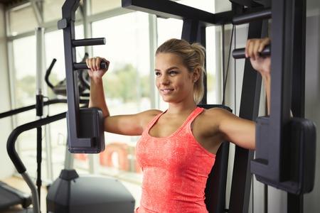 Mooie vrouw die borstoefeningen in gymnastiek doet Stockfoto - 64451491
