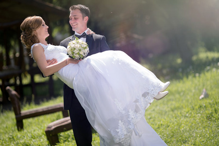 Groom carrying bride outdoors and smiling Stock Photo