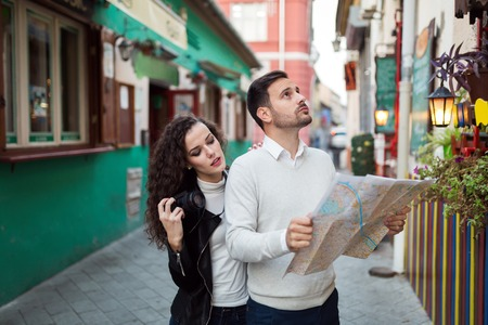 Tourist couple searching for destination by looking at map