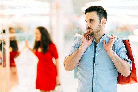 shopping spree: Frustrated man waiting for spouse to finish shopping spree Stock Photo