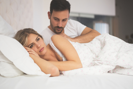 Relationship crisis in bed with feeling of guilt Stock Photo