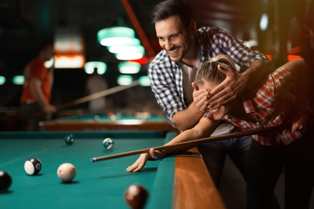 Couple playing snooker together