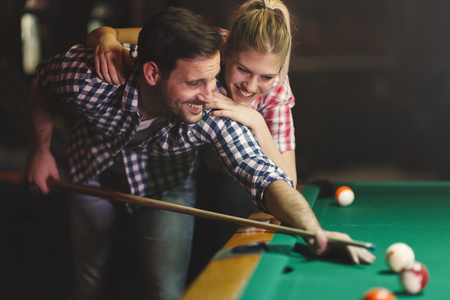 cue sticks: Couple playing snooker together