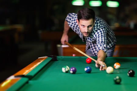 Handsome man playing pool in pub