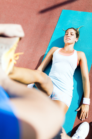Young beautiful sportswoman having a strain and being stretched by trainer Stock Photo