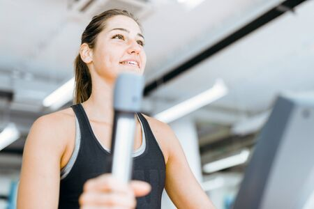 elliptical: Beautiful young lady using the elliptical trainer in a gym in a positive mood