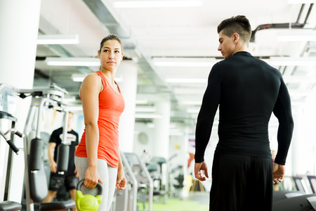 Young male trainer giving instructions to a woman in a gym and being supportive