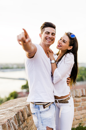 Happy couple pointing in a direction  and smiling Stock Photo