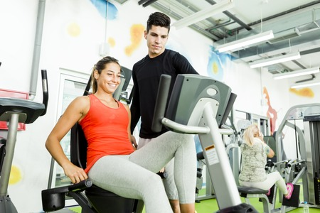 Beautiful young woman instructed by a handsome man in a gym while using a bicycle