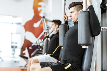 Two handsome men working out in a beautiful fitness center