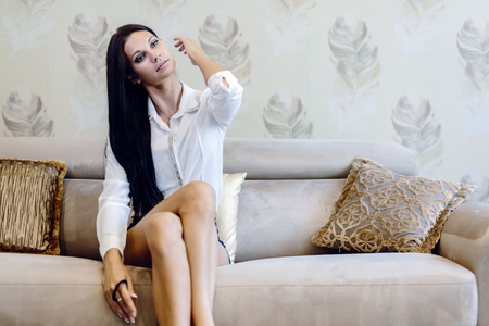 Elegant and sexy woman sitting on a sofa in a luxurious room and fixing her hair Stock Photo