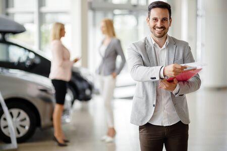 car retailer: Salesperson at car dealership selling vehichles