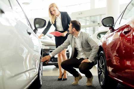 car salesperson: Car salesperson explaining tire and rim options Stock Photo