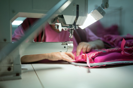 textile industry: Worker in textile industry sewing on machine