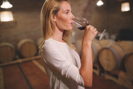 Female tasting wine in winery cellar