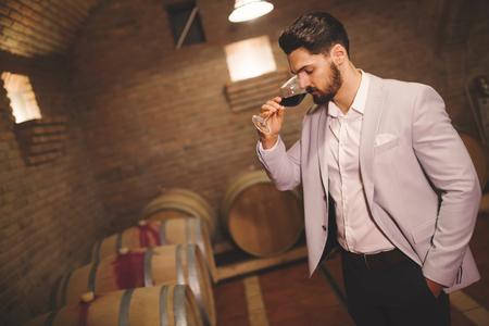 Winemaker inspecting wine in winery basement