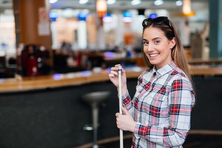 Beautiful brunette chalking billiard cue Stock Photo