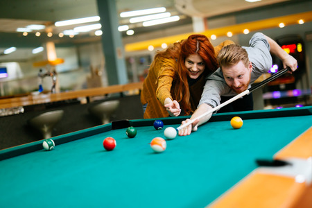 Couple playing billiards and bonding