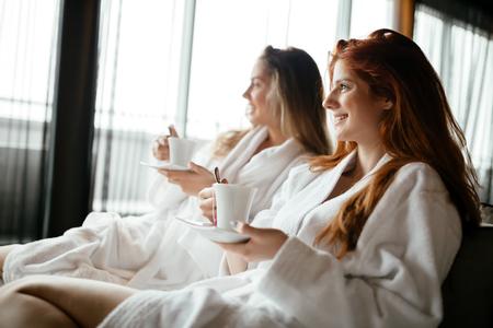 Women in bathrobes enjoying tea and wellness weekend