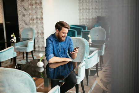 Man waiting for woman in restaurant and checking phone