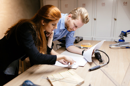 woman handle success: Creative designers working in workshop while standing at the desk full of tools and discussing ideas