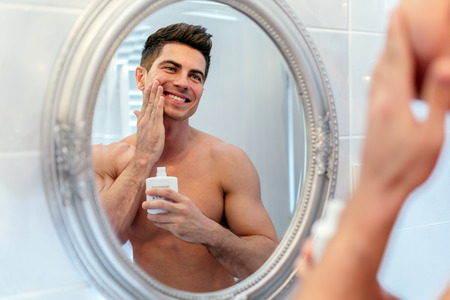 Healthy positive male treating sking with lotion after shaving