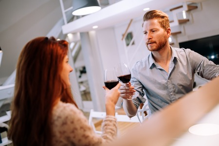 toasting wine: Beautiful couple celebrating moving in to new apartment by toasting wine