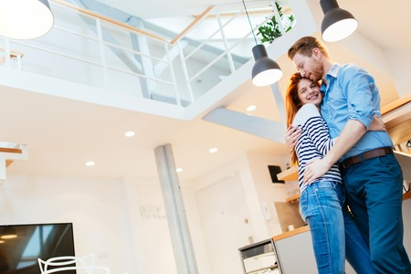 luxurious: Couple enjoying their new luxurious home and hugging in living room