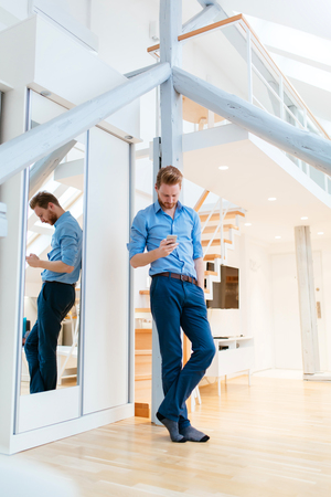 Man using phone in beautiful modern apartment wearing shirt