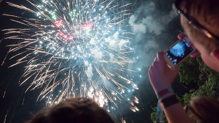 女性の携帯電話で花火の祭典を撮影 写真素材