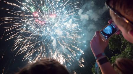 Mujer fotografiando celebración de fuegos artificiales con teléfono Foto de archivo - 67857672