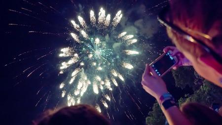 Mujer fotografiando celebración de fuegos artificiales con teléfono Foto de archivo - 67857673