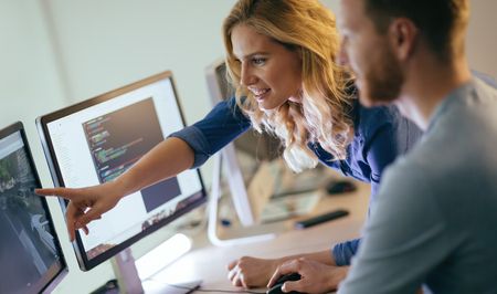 Programmers cooperating at  IT company developing apps Stock Photo