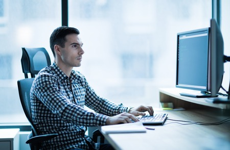 Professional software developer working in office at desk Stock Photo
