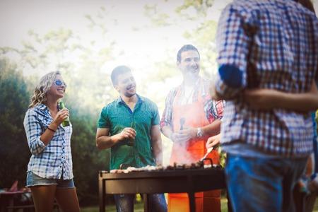Amigos que se divierten asar la carne disfrutando de una fiesta de barbacoa Foto de archivo - 71323693