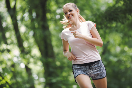 staying fit: Beautiful jogging woman in nature staying fit and energetic